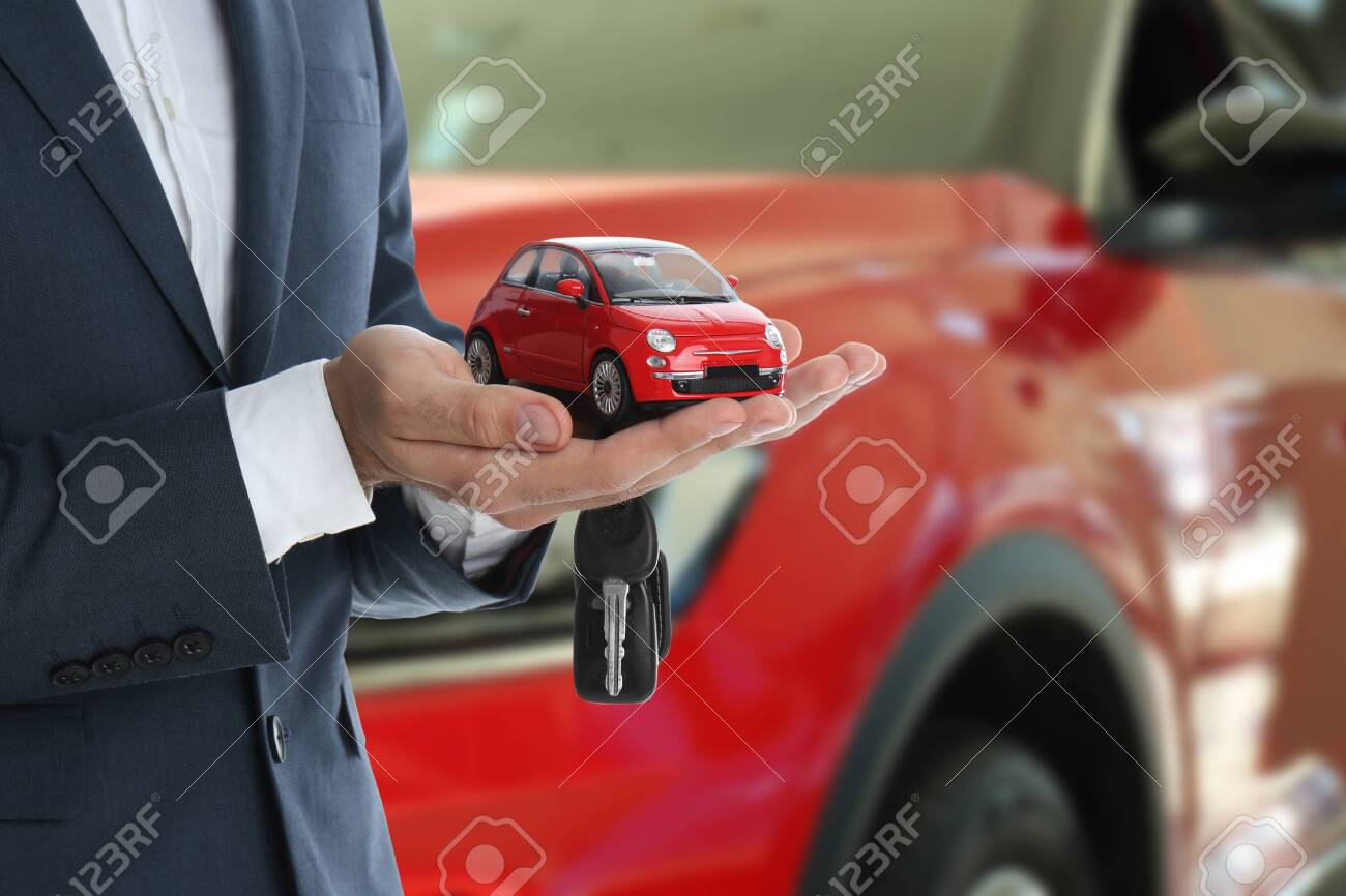 Car buying. Man holding key and model against blurred automobile, closeup - 154496227
