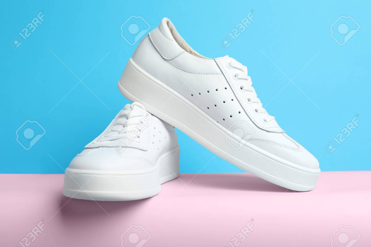 Stylish White Shoes On Pink Paper