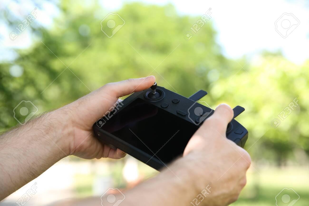 Man holding new modern drone controller outdoors, closeup of hands - 154360412