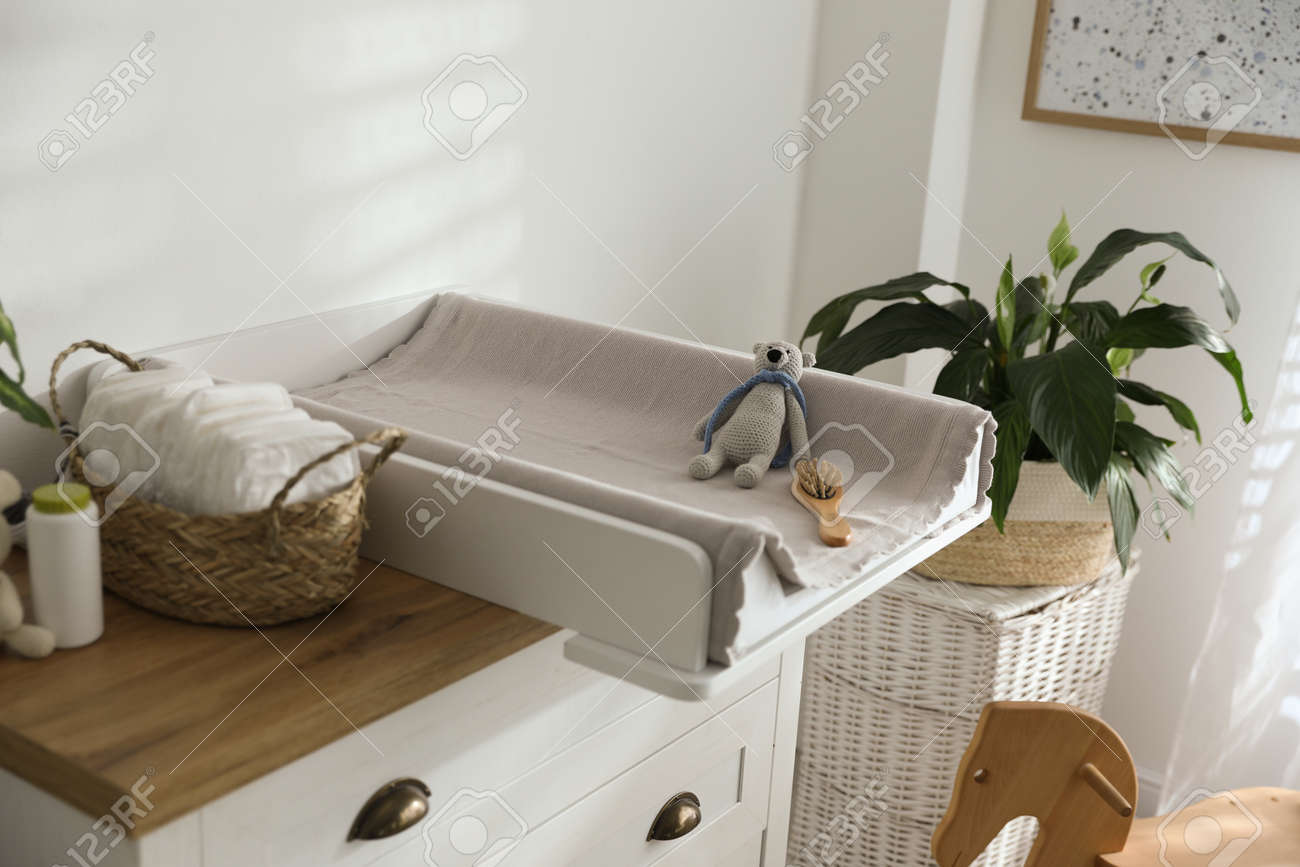 Chest of drawers with changing pad and tray in nursery. Baby room interior design - 155887567