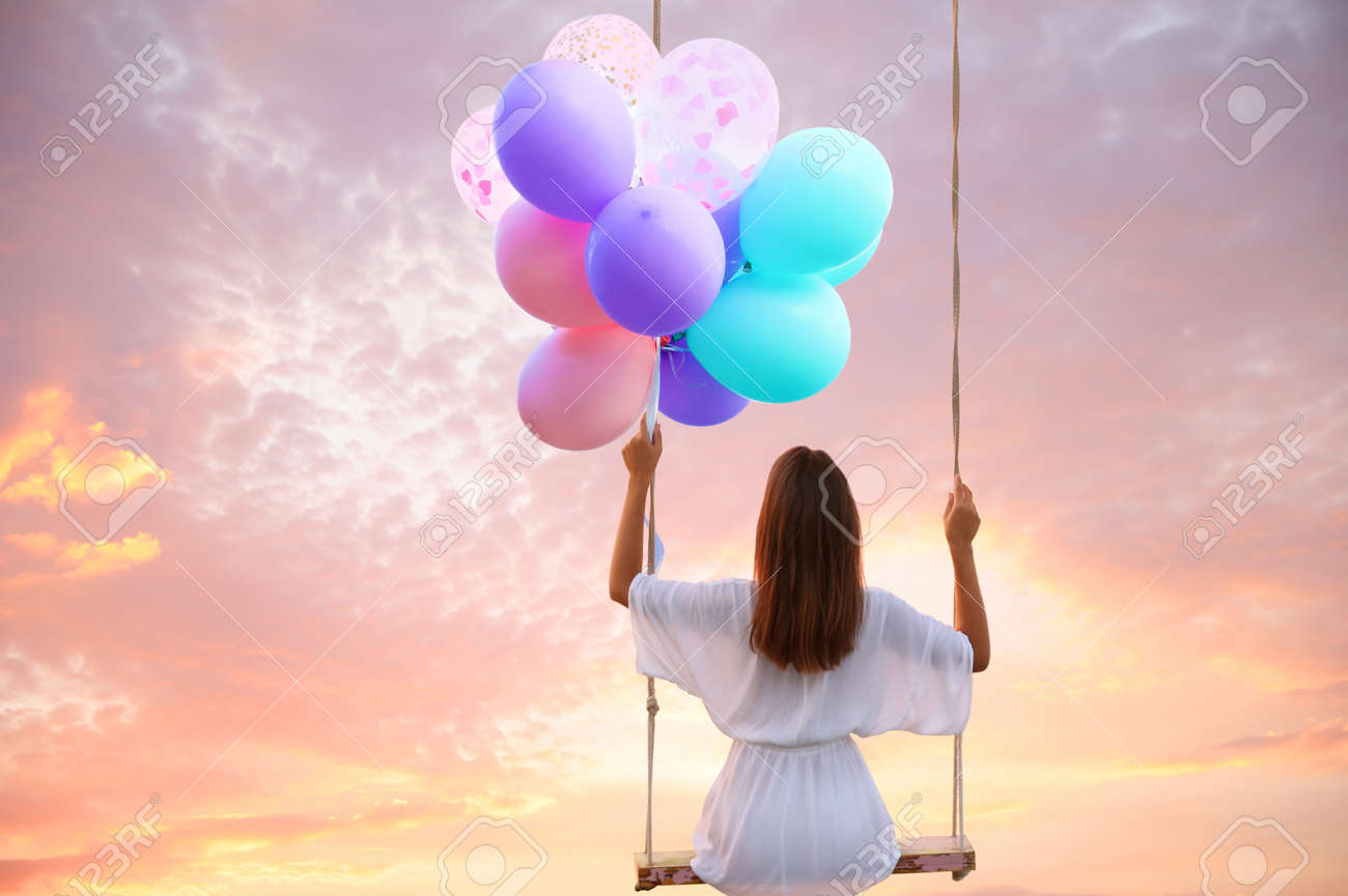Dream world. Young woman with bright balloons swinging, sunset sky on background - 154797826