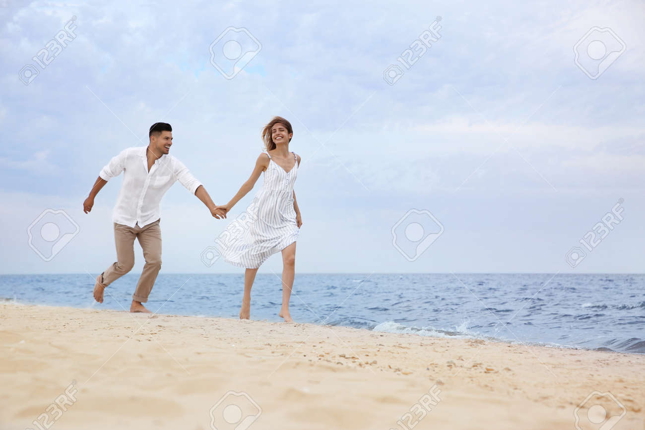 Happy couple running on beach, space for text. Romantic walk - 155320138