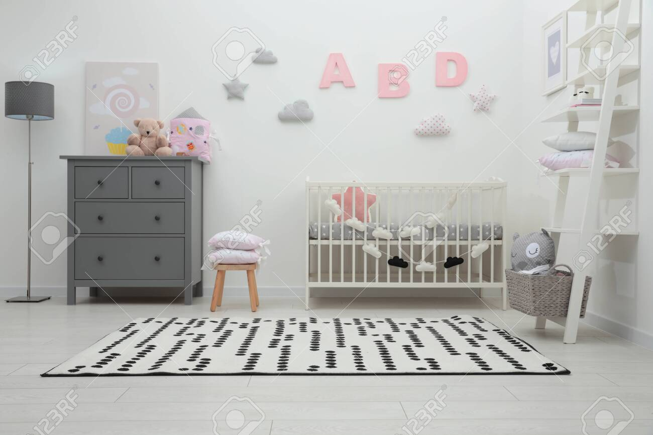 Cute baby room interior with crib and chest of drawers near white wall - 155373231