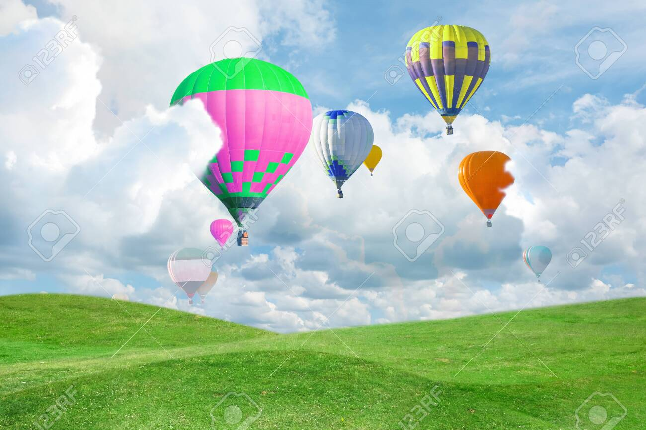 Fantastic dreams. Hot air balloons in sky with fluffy clouds over green meadow - 155444460