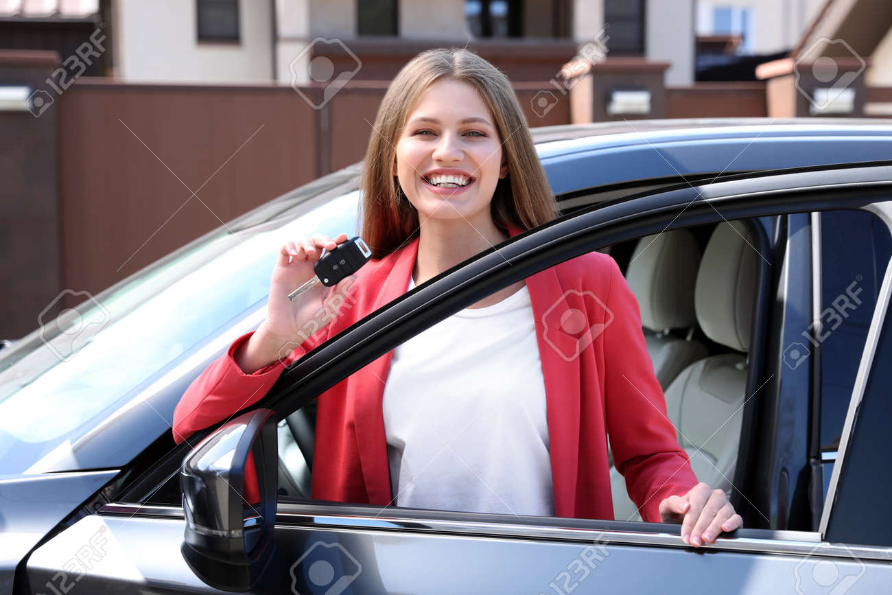 Happy woman with car key near her new auto outdoors - 155442696