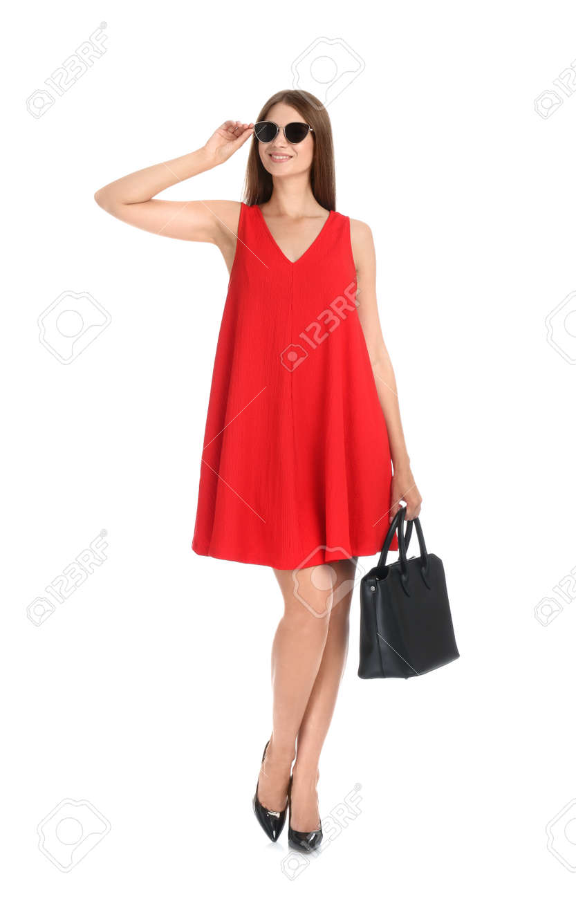 Young woman wearing stylish red dress with elegant bag on white background - 155834427