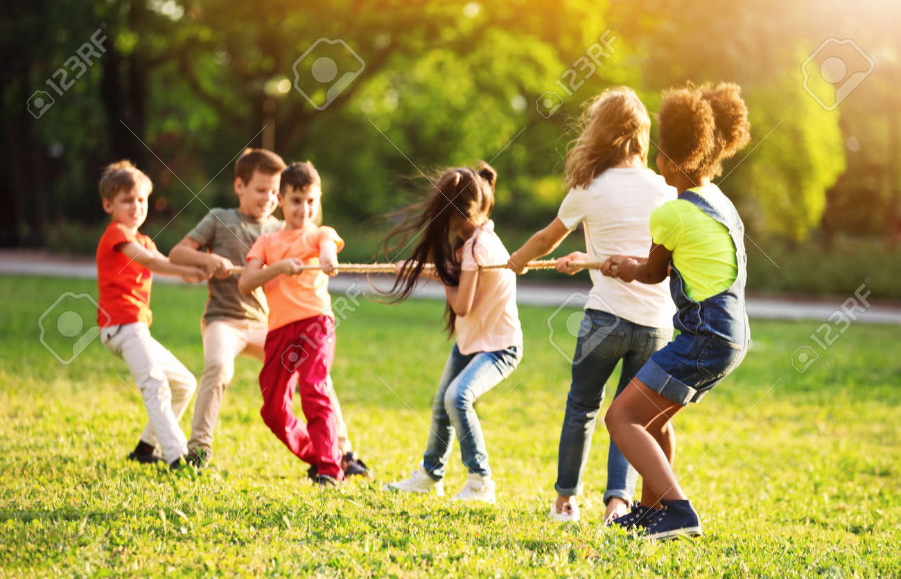 School holidays. Group of happy children playing with rope outdoors - 156128935