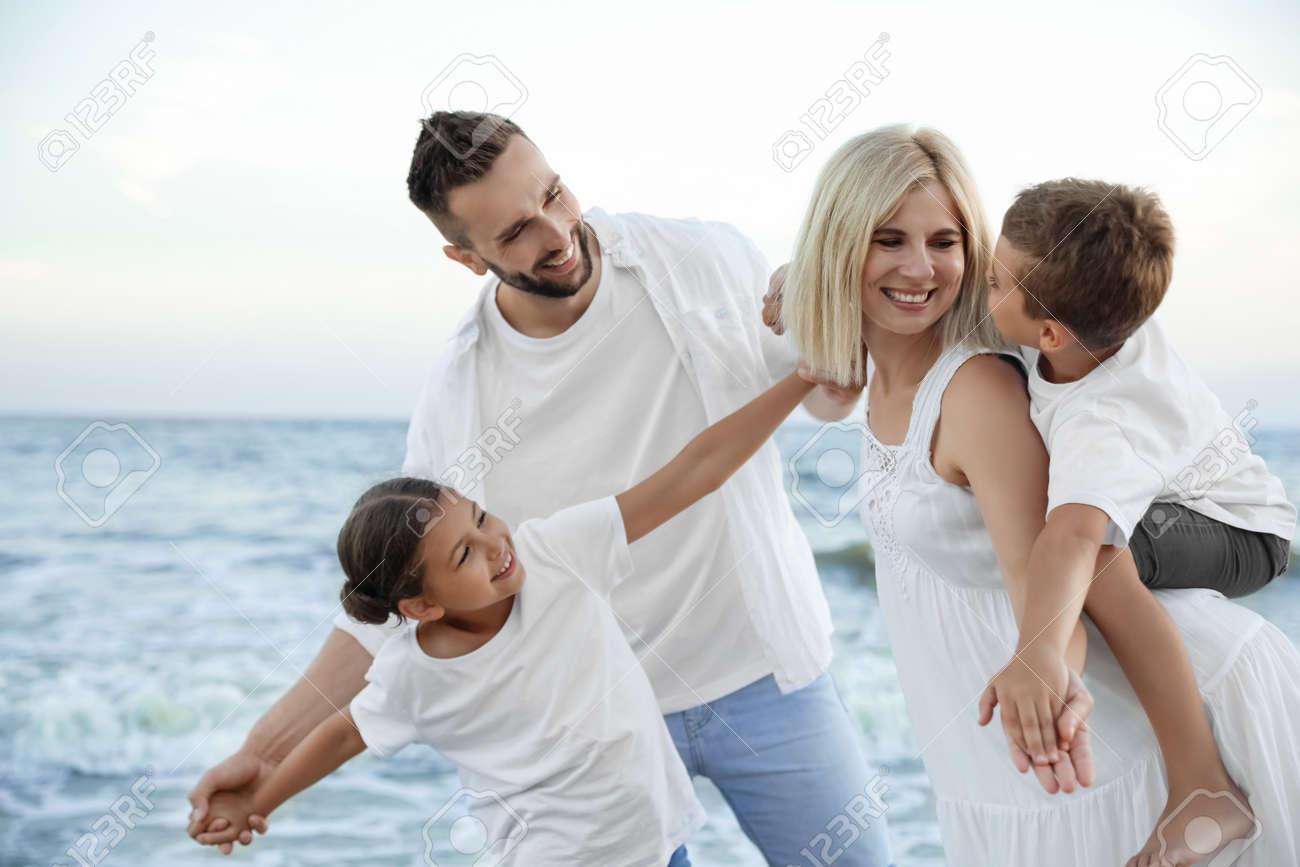 Happy family having fun on beach near sea - 158358114