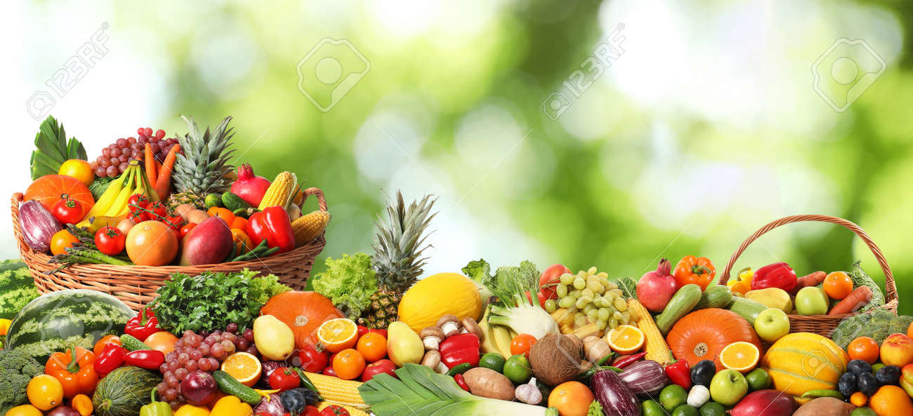 Assortment of fresh organic vegetables and fruits on blurred green background - 158619542