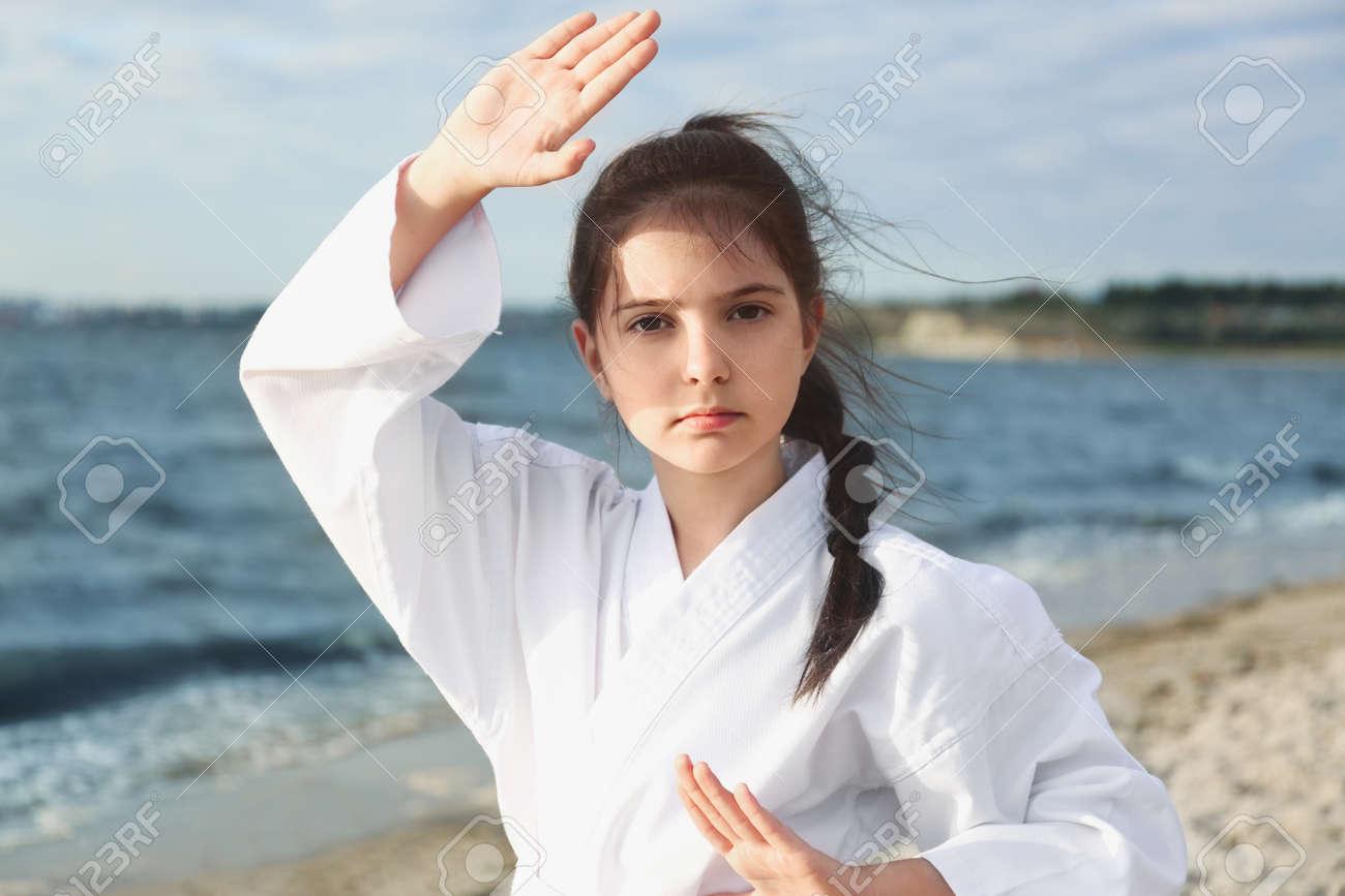 Cute little girl in kimono practicing karate near river - 158637067