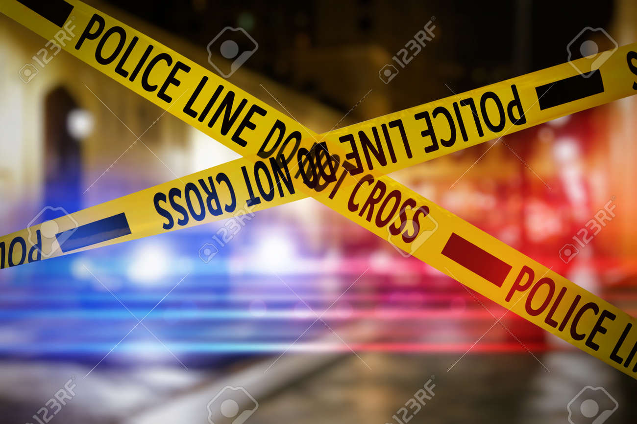 Yellow law enforcement tape isolating crime scene. Blurred view of city street, toned in red and blue police car lights - 158920409