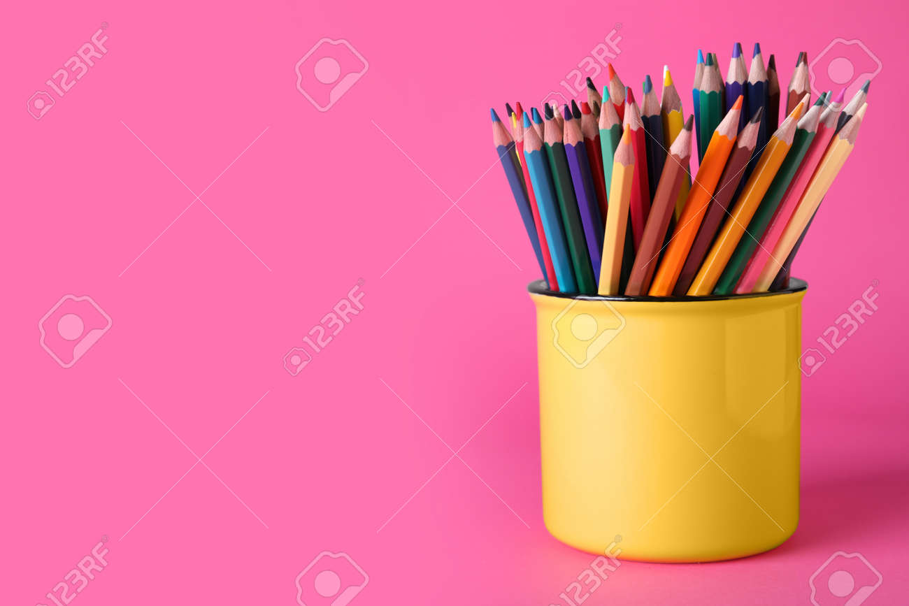 Colorful pencils in mug on pink background. Space for text - 159064548