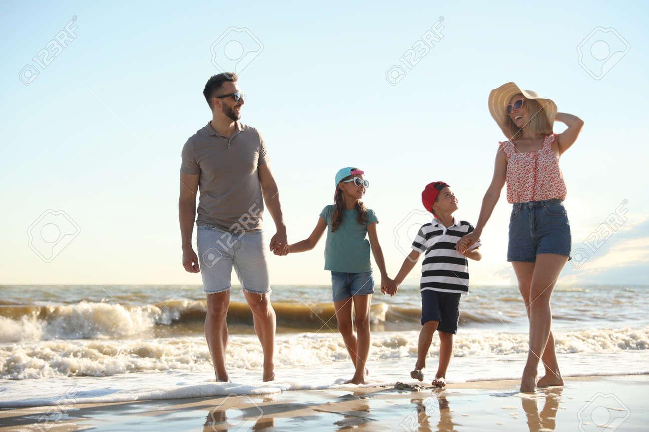 Happy family walking on sandy beach near sea - 159301778