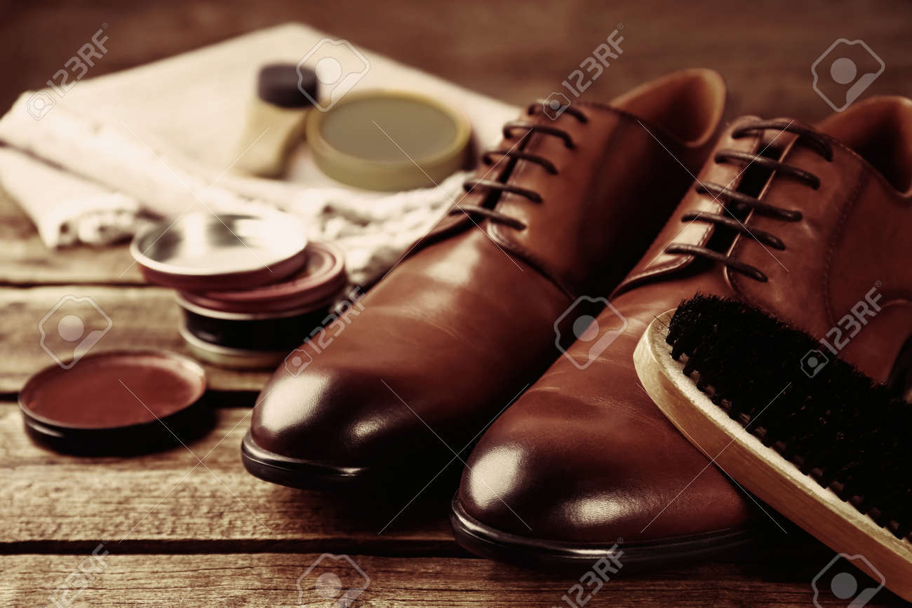 Shoe care accessories and footwear on wooden background - 160450728