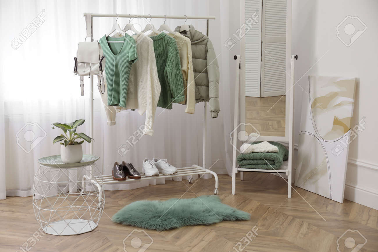 Rack with stylish warm clothes and shoes near mirror in dressing room - 161236405