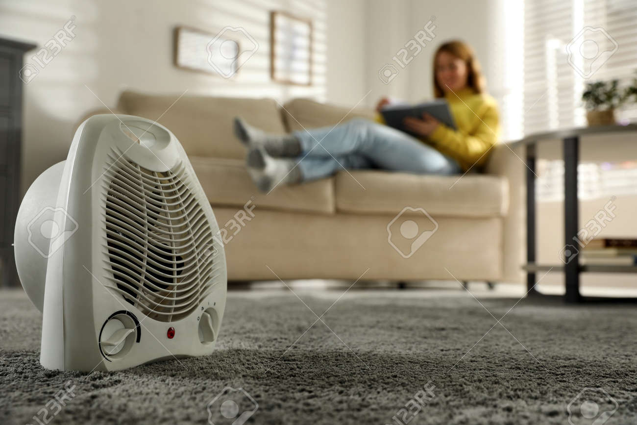 Woman reading book in living room, focus on electric fan heater - 162336961