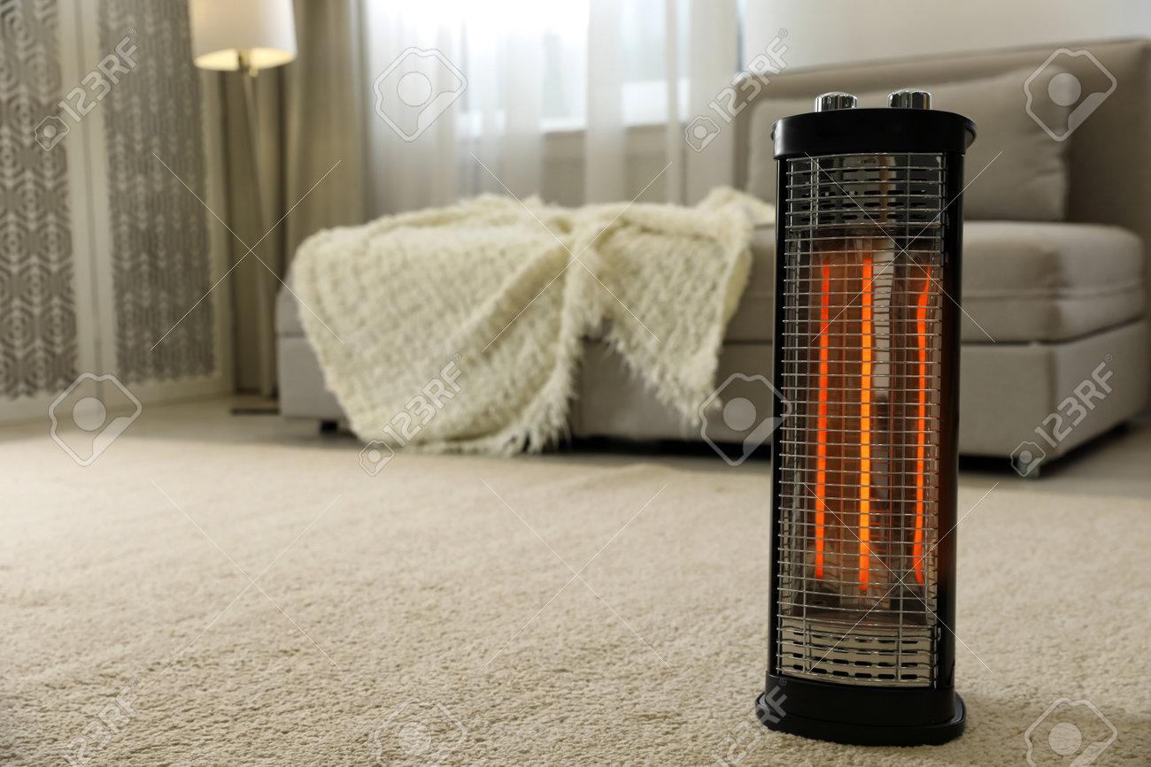 Modern electric halogen heater on floor in living room interior - 162214827