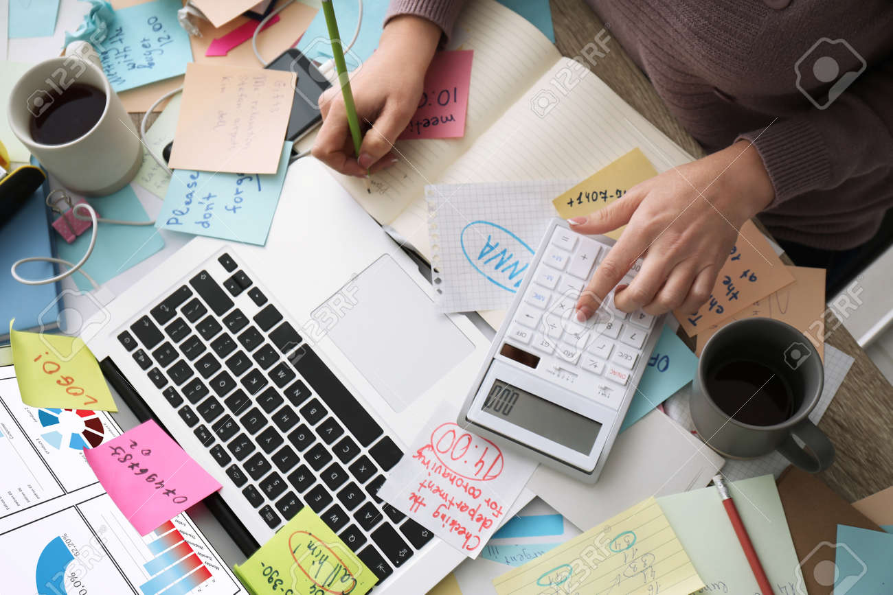 Overwhelmed woman working at messy office desk, top view - 163826783
