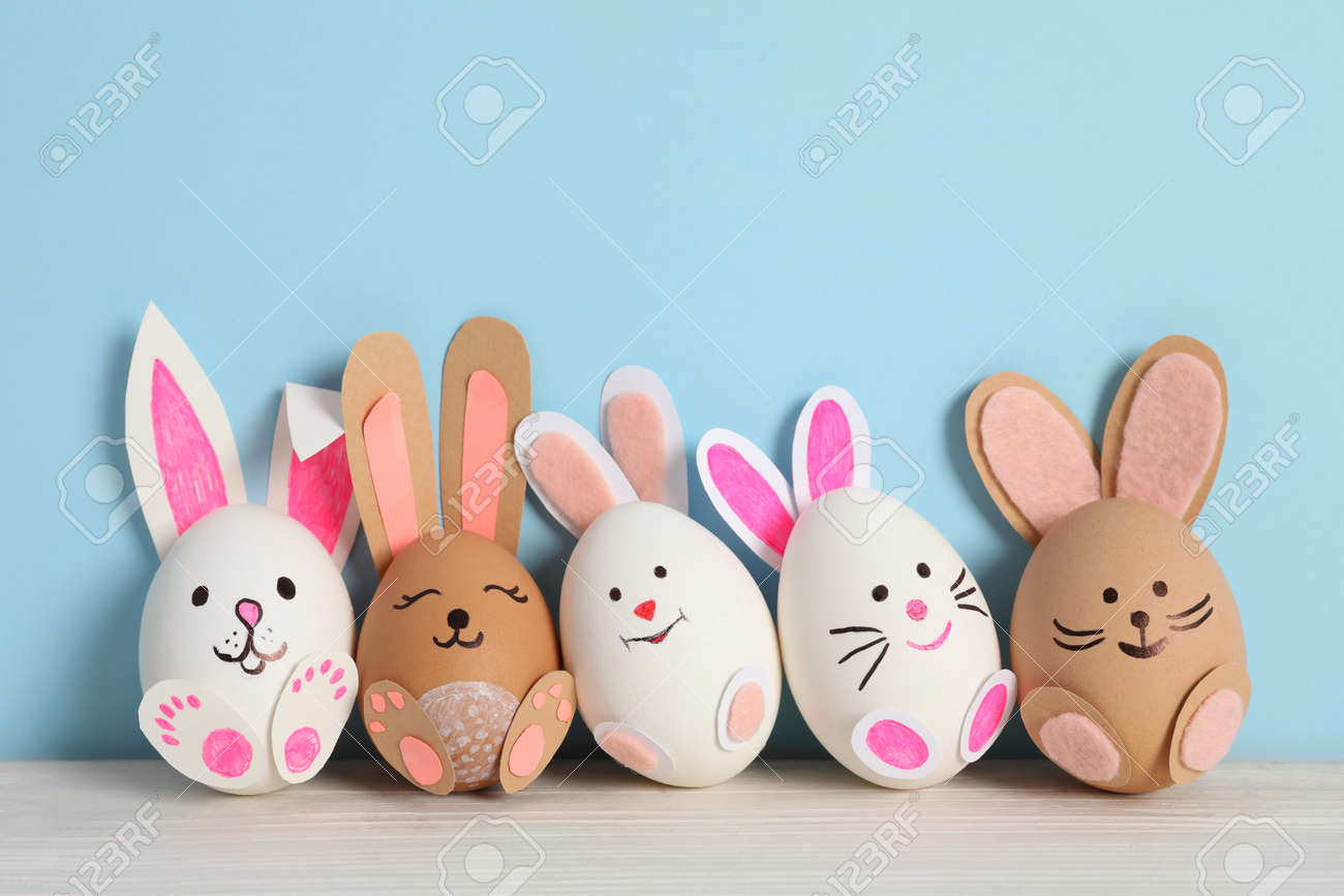 Eggs as cute bunnies on white wooden table against light blue background. Easter celebration - 164456060