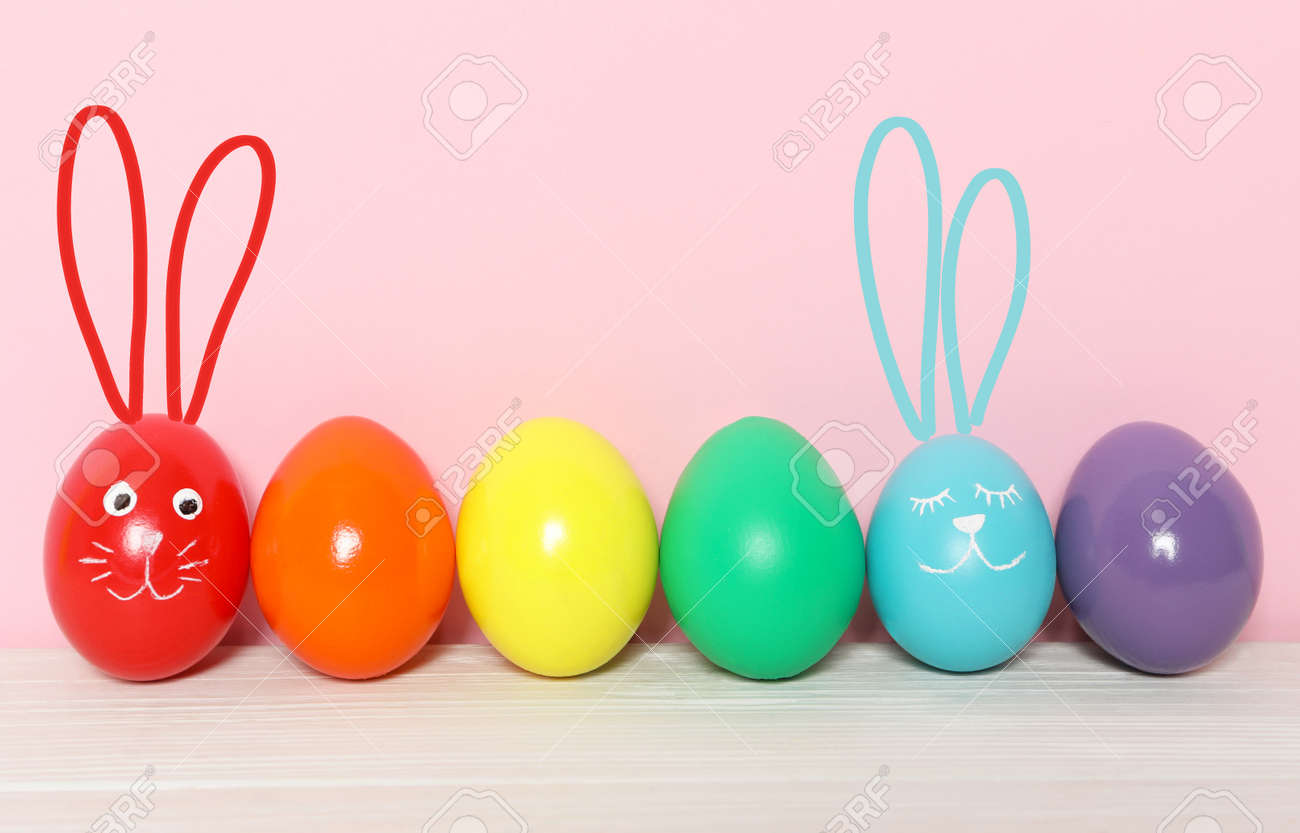 Two eggs with drawn faces and ears as Easter bunnies among others on white wooden table against pink background - 165327990