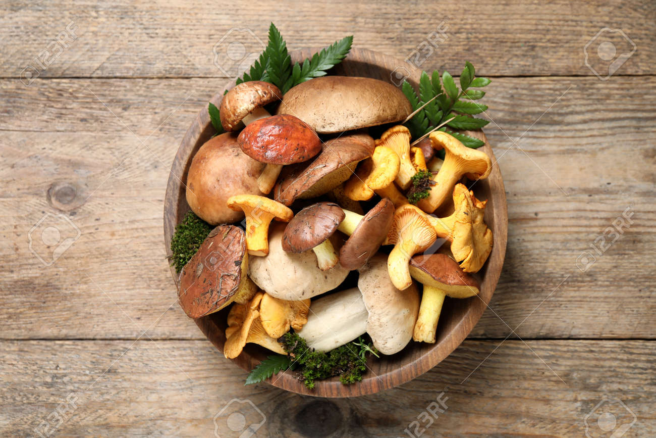 Bowl with different mushrooms on wooden table, top view - 165097918
