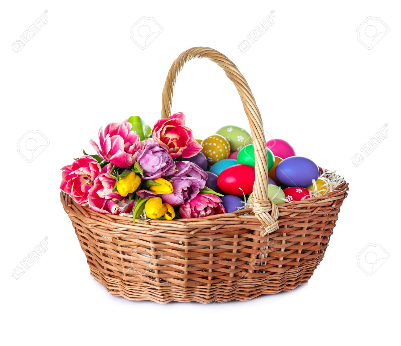 Wicker basket with bright painted Easter eggs and spring flowers on white background - 165362404