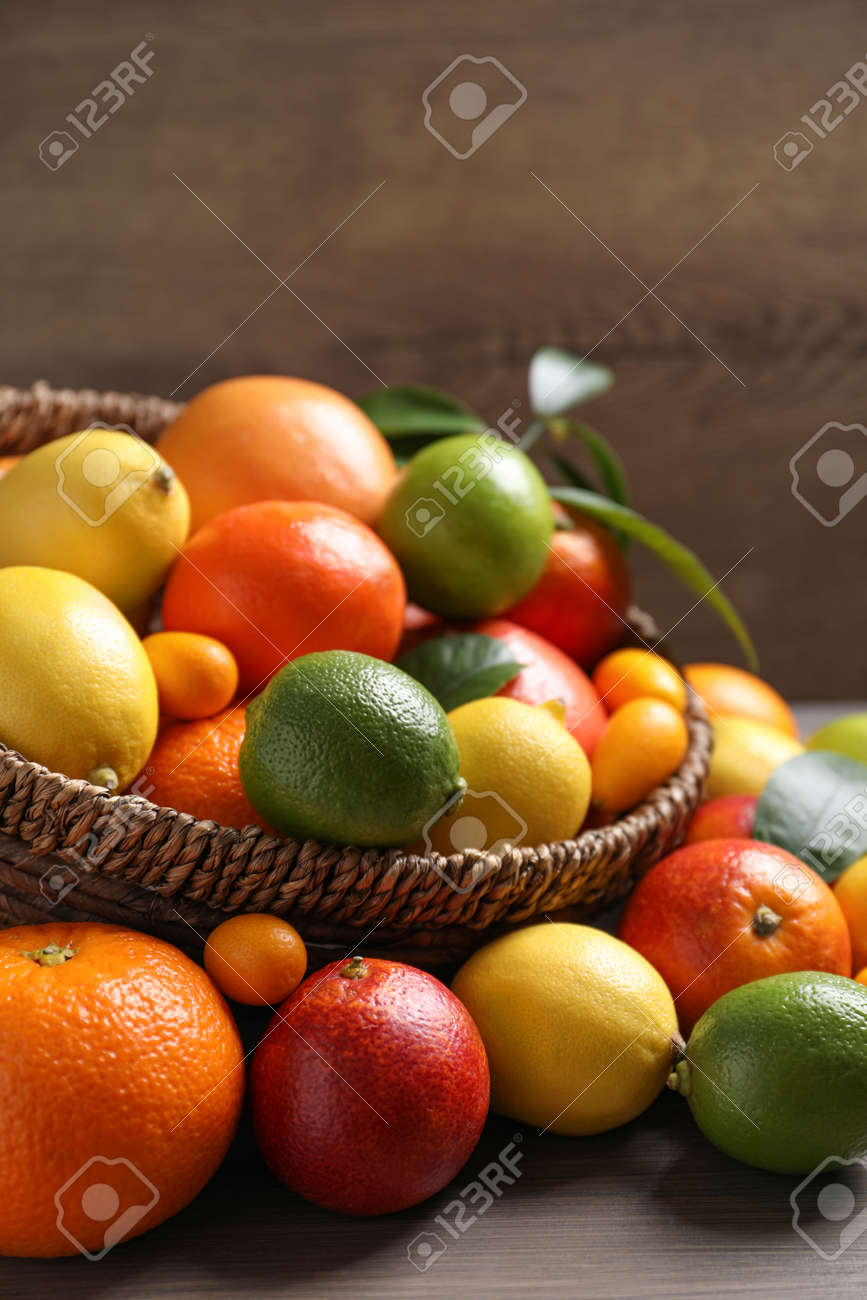 Different ripe citrus fruits on wooden table - 165456246