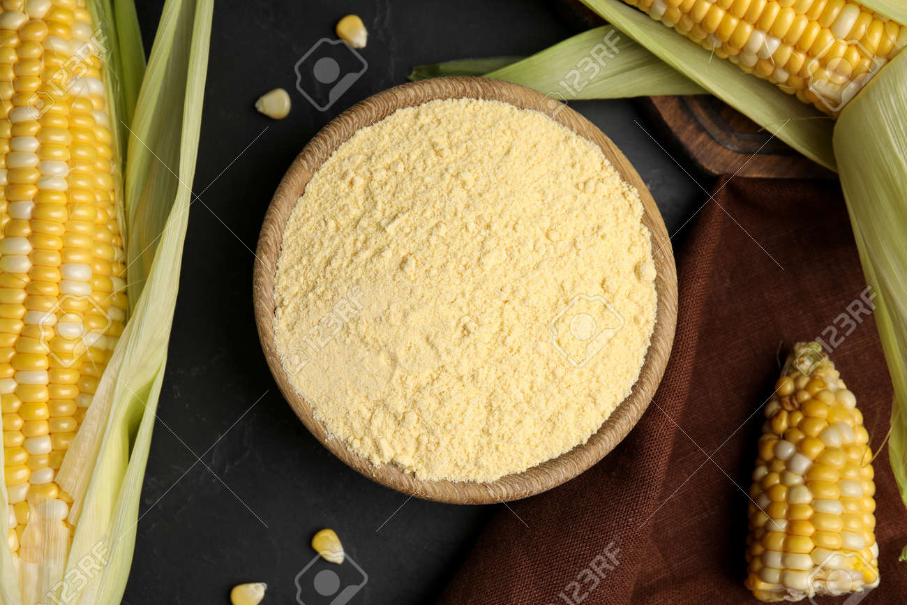 Corn flour in bowl and fresh cobs on black table, flat lay - 165456739
