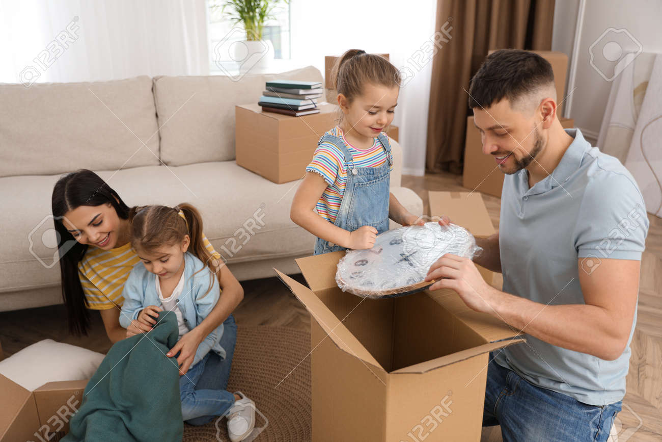 Happy family unpacking moving boxes at their new house - 166677698