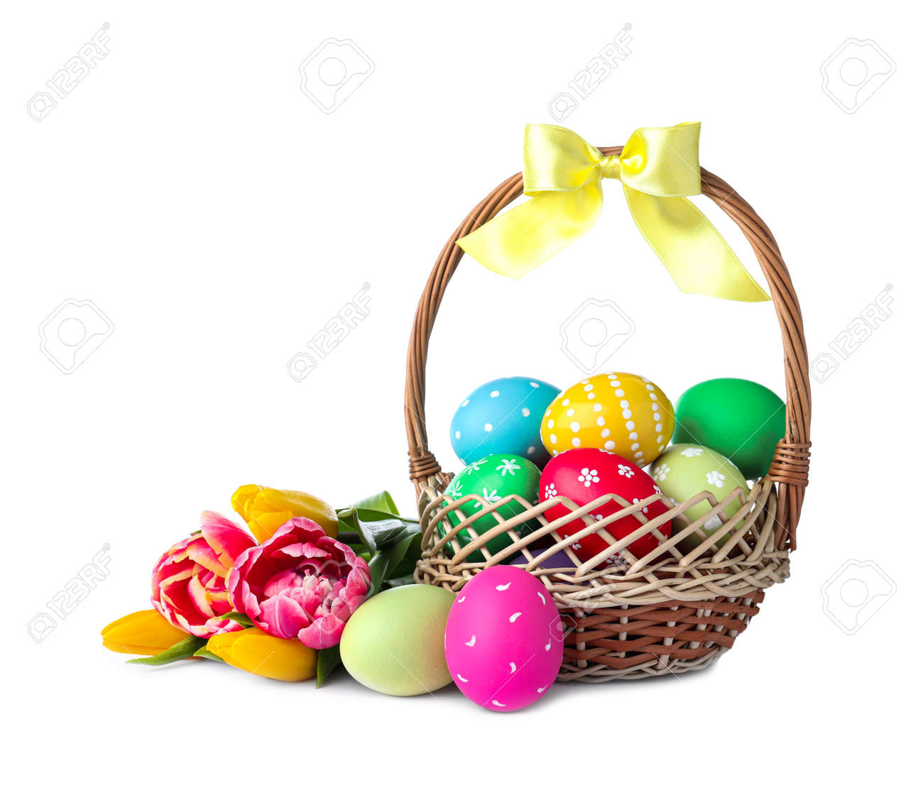 Wicker basket with bright painted Easter eggs and spring flowers on white background - 165596940