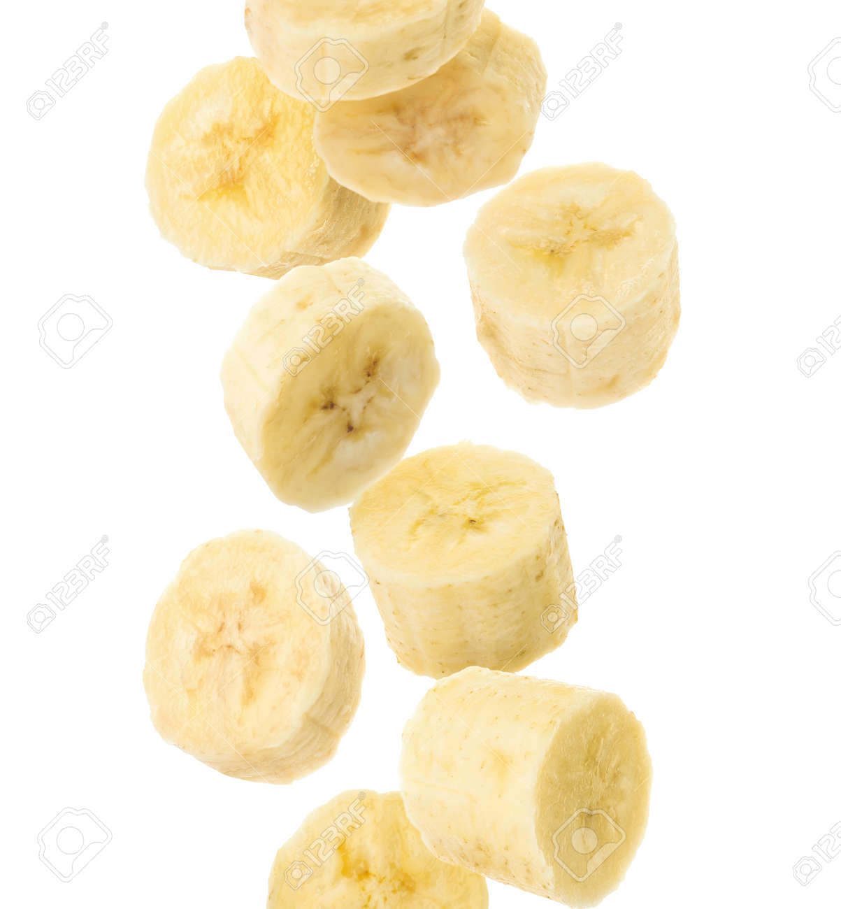 Slices of tasty ripe banana falling on white background - 165621289