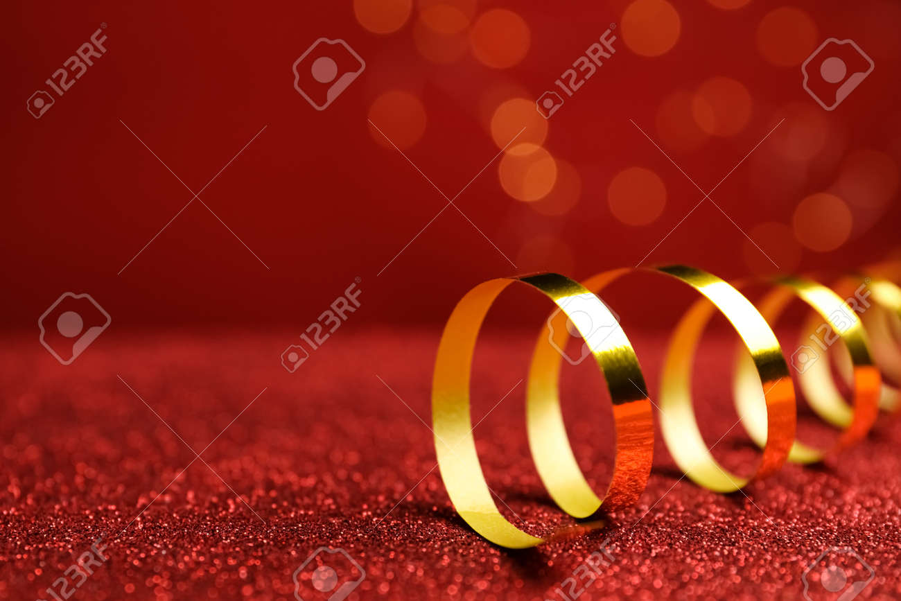 Shiny golden serpentine streamer on red table against blurred lights, closeup. Space for text - 165789742