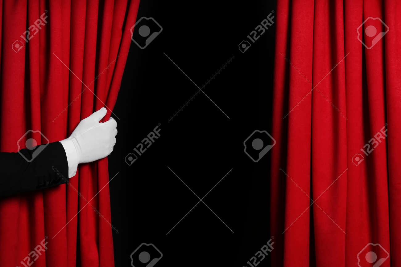 Person opening red front curtains on black background, closeup. Space for text - 166450509