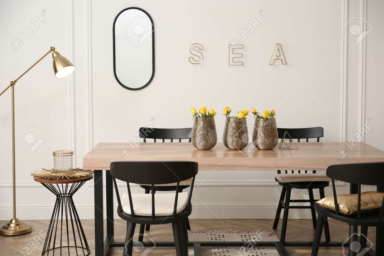 Stylish wooden dining table and chairs in room. Interior design - 166656688