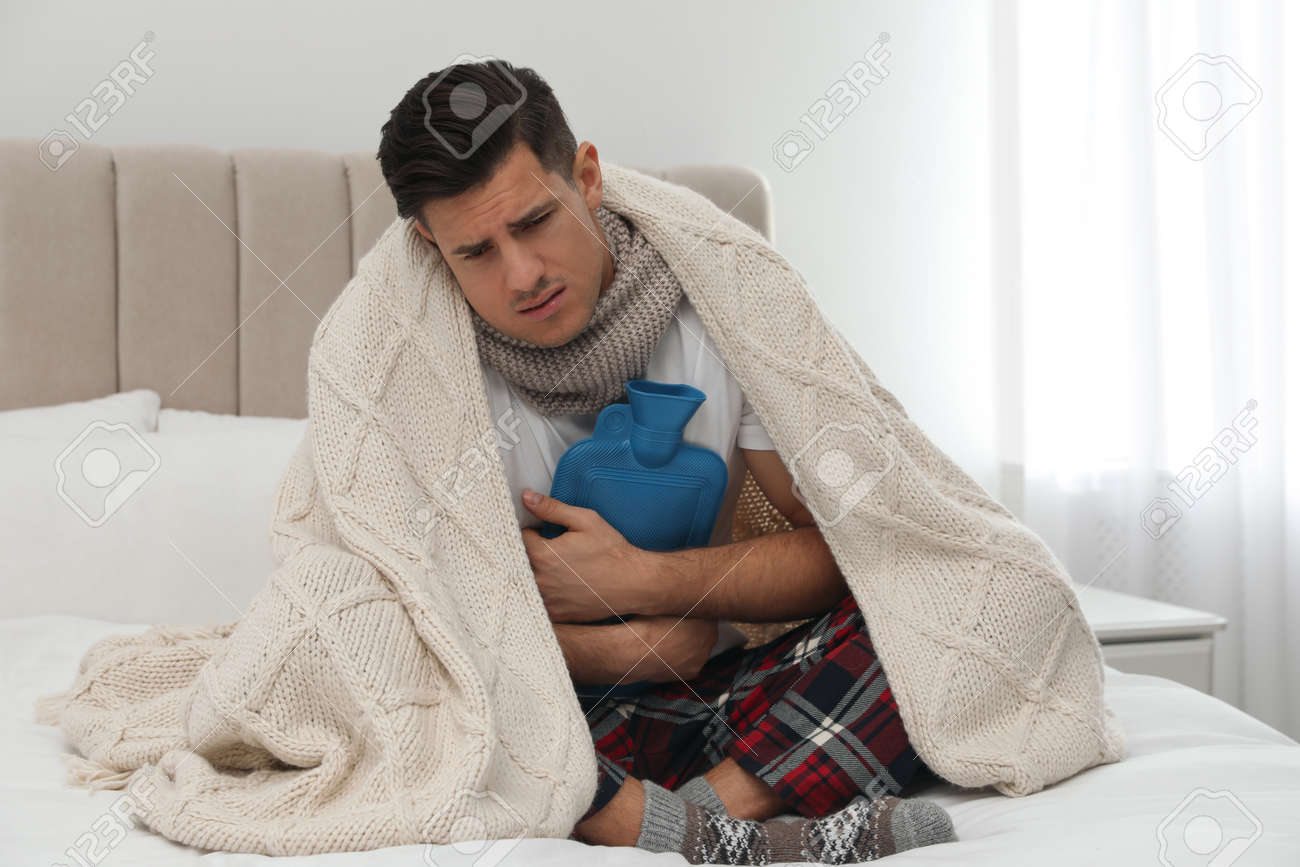 Ill man with hot water bottle suffering from cold at home - 167257646