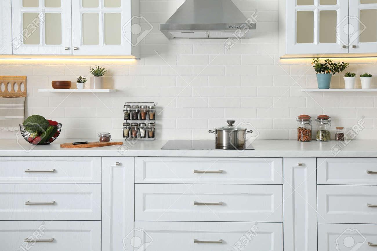 Elegant kitchen interior with modern stove and stylish furniture - 167344997