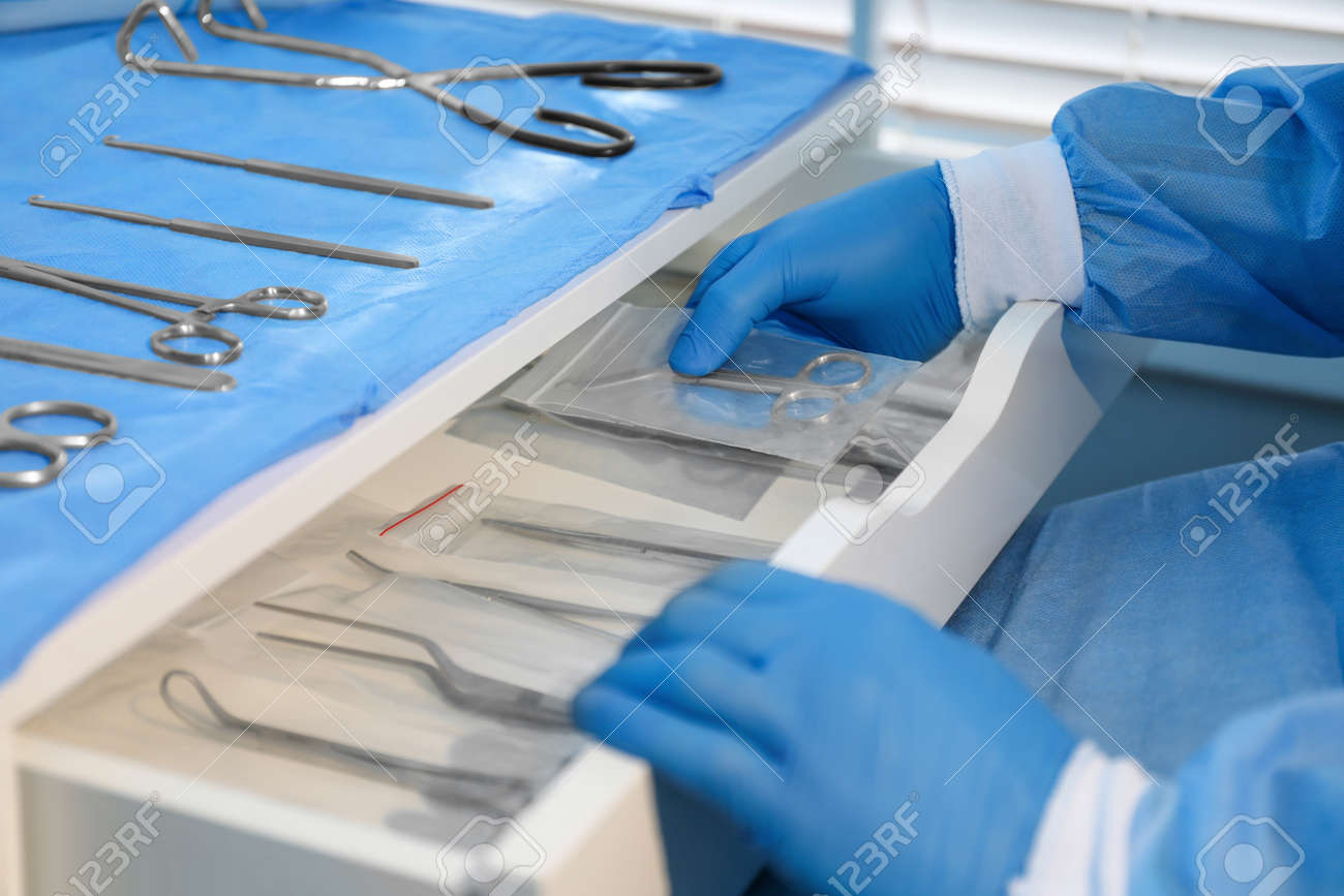 Doctor putting Pott's scissors into drawer indoors, closeup. Table with different surgical instruments - 167495079