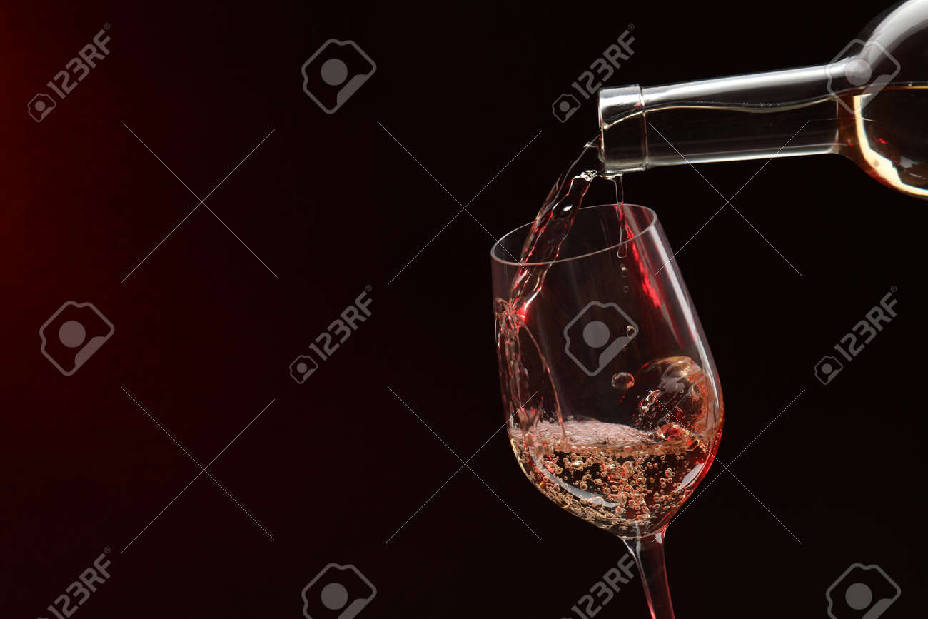 Pouring white wine from bottle into glass on dark background, space for text - 168516460