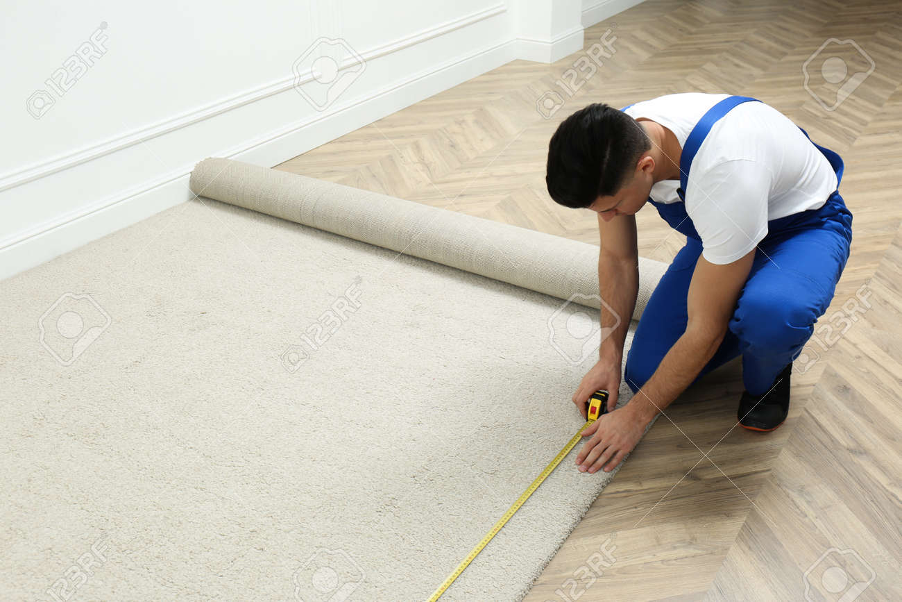 Worker with measuring tape installing new carpet indoors - 168659002