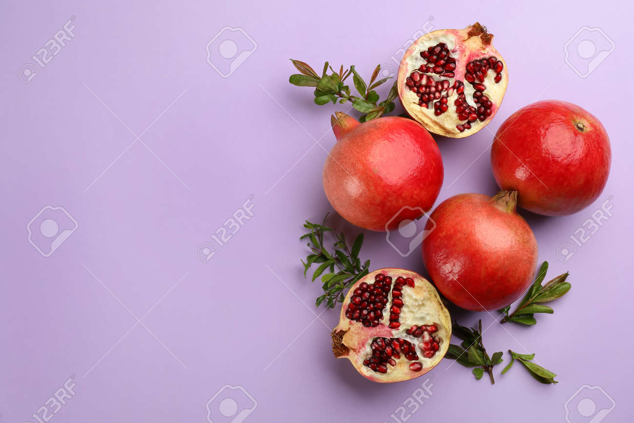 Flat lay composition with ripe pomegranates on violet background. Space for text - 168659471