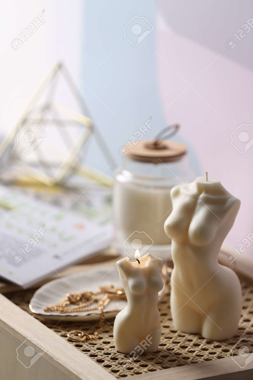 Beautiful body shaped candles and jewelry on tray indoors - 169547905