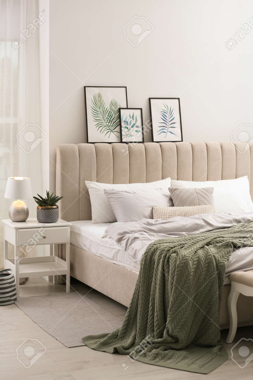 Bed with stylish gray linens near white wall in room - 169708560