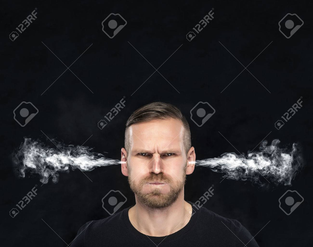 Angry man with smoke or fume coming out from his ears on dark background. - 51573304