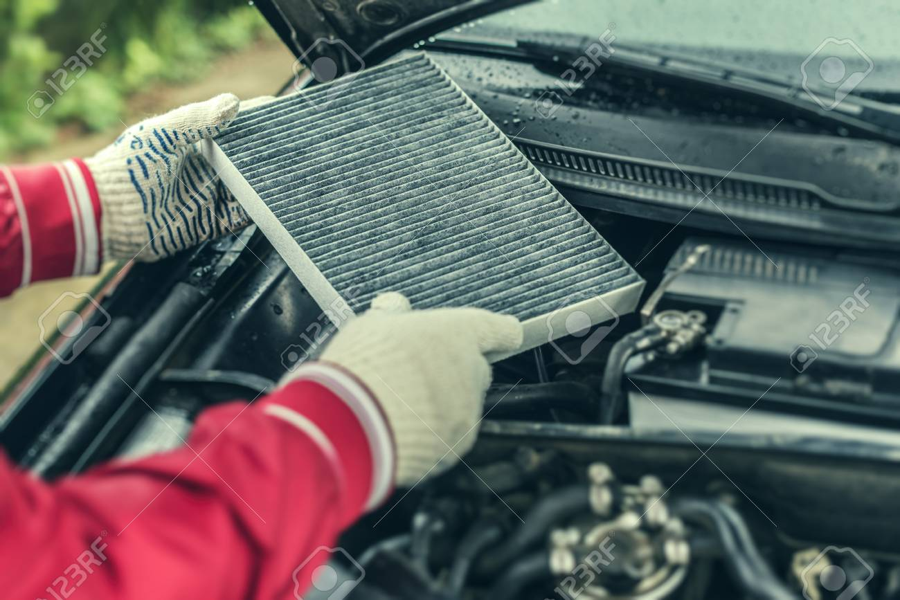 The auto mechanic replaces the cars interior filter. - 101663064