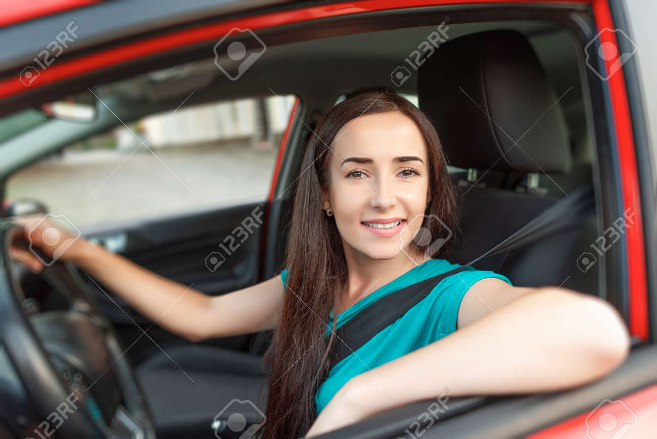 Happy beautiful woman is driving a car. - 166401516