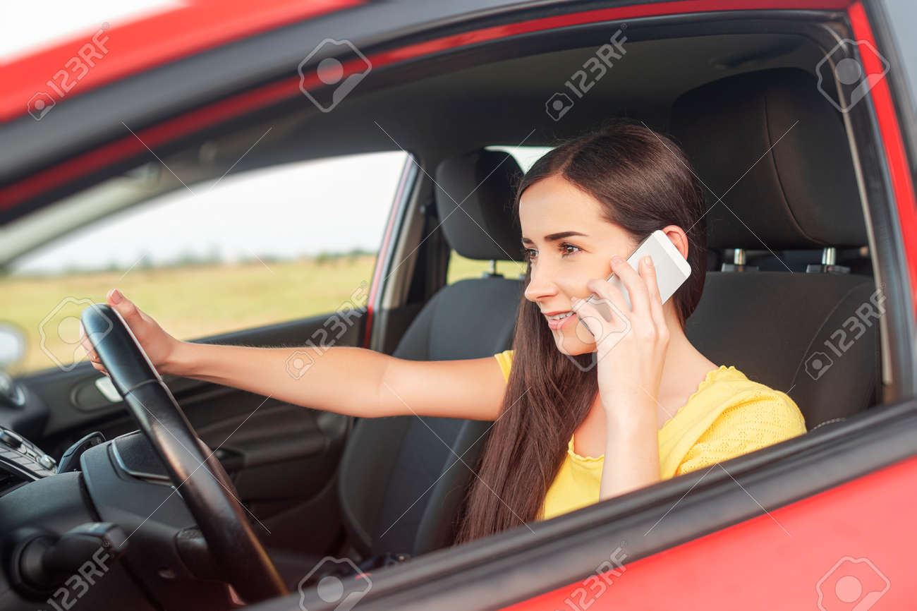 Woman talking on the phone while driving a car. - 167106134