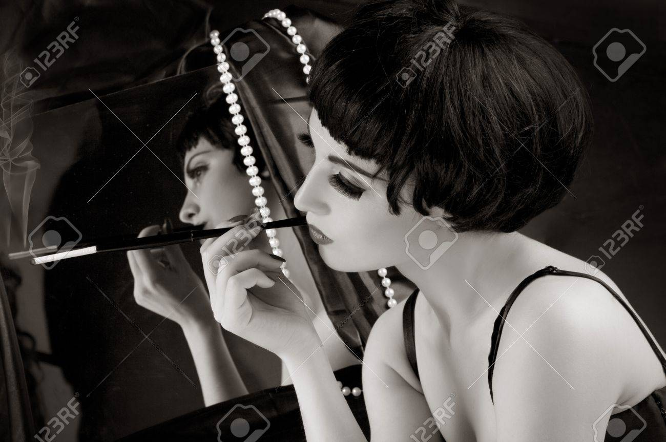Beautiful brunette girl with cigarette before a mirror. White and Black Stock Photo - 9503894