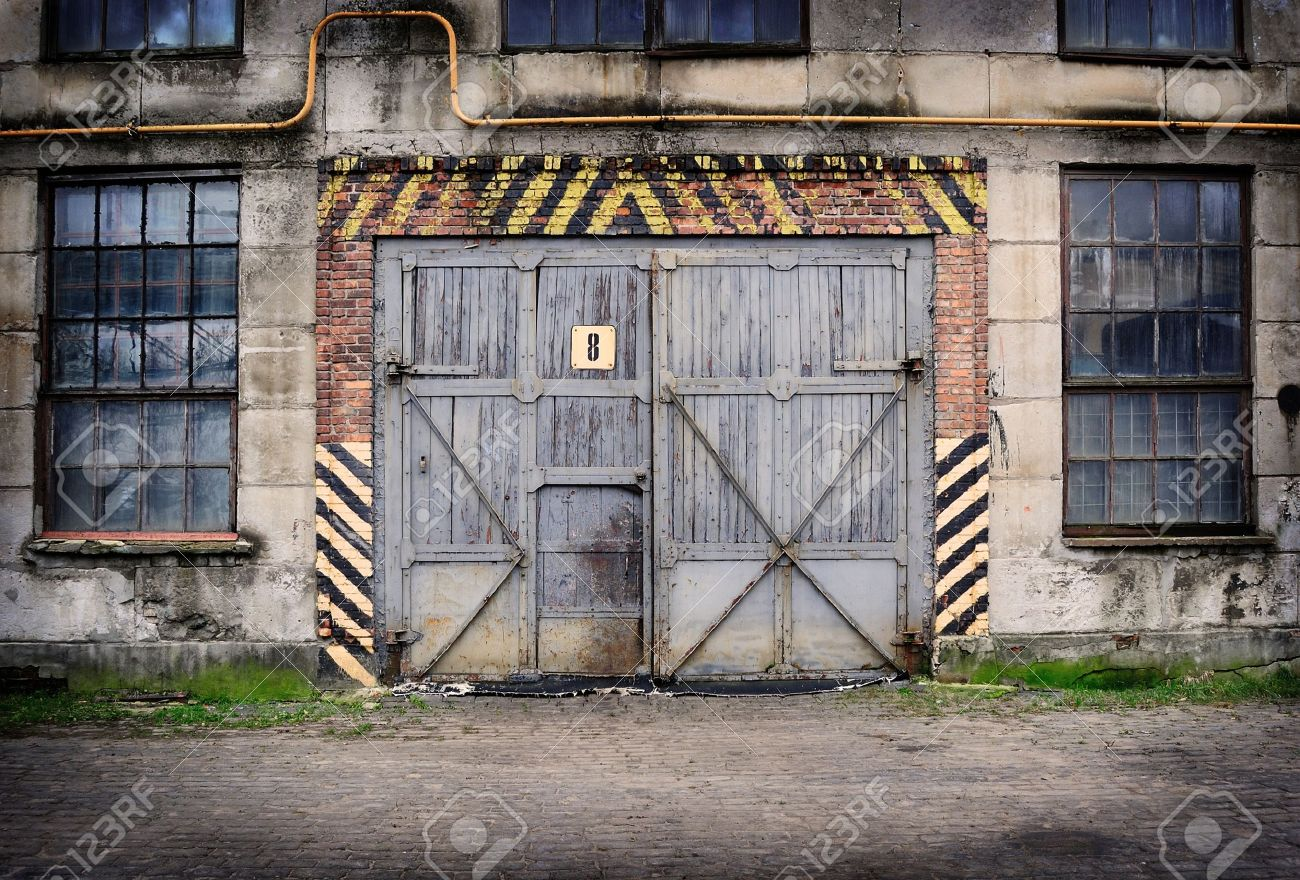 Abandoned old factory with closed door and windows - 17932823
