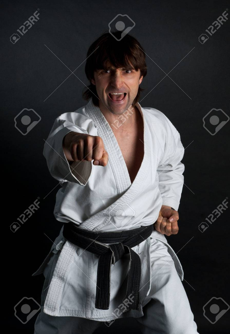 Man in a kimono with a black belt doing forward kick on a black background - 29467899