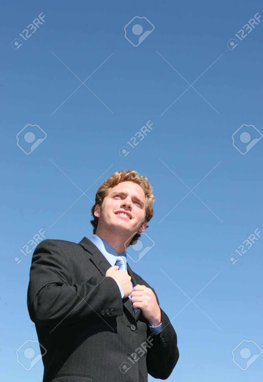 Business man in black suit and blue shirt holding onto the inside of his suit, looking up - 2543838